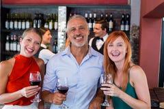 Portrait des amis se tenant au compteur de barre avec un verre de vin rouge Image libre de droits