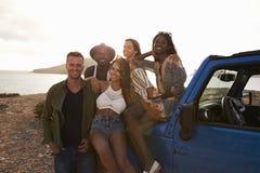 Portrait des amis se tenant prêt la voiture à couvercle serti sur des falaises Photos libres de droits