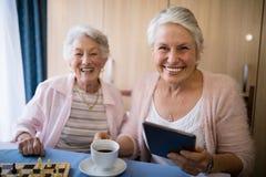 Portrait des amis supérieurs de sourire ayant le café tout en jouant des échecs Photographie stock libre de droits
