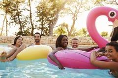 Portrait des amis sur Inflatables dans la piscine extérieure Photos stock