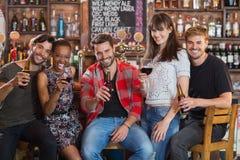Portrait des amis tenant des bouteilles à bière et des verres à vin Photos stock