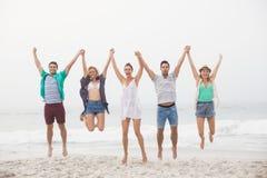 Portrait des amis tenant des mains et sautant sur la plage Photographie stock