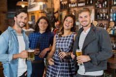 Portrait des amis tenant des verres et des bouteilles de bière dans le bar Photos stock