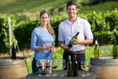 Portrait des amis tenant le verre à vin et la bouteille par la table contre le vignoble Photos libres de droits