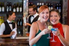 Portrait des amis tenant un cocktail devant le compteur de barre Photographie stock libre de droits