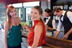Portrait des amis tenant un cocktail devant le compteur de barre Photo libre de droits