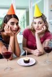 Portrait des amis tristes s'asseyant à la table pendant la fête d'anniversaire Photographie stock libre de droits