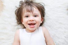 Portrait des 2 années heureuses d'enfant se trouvant sur la fourrure blanche Photographie stock