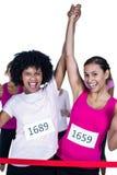 Portrait des athlètes gais de gagnant croisant la ligne d'arrivée avec des bras augmentés photo stock