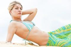 Portrait des blonden Mädchens, das auf dem Sand liegt Lizenzfreie Stockfotos