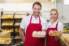 Portrait des boulangers de sourire ayant une pâtisserie Image libre de droits