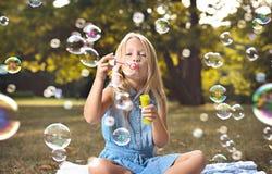 Portrait des bulles de savon de soufflement de fille gaie photographie stock libre de droits