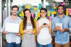Portrait des cadres de sourire à l'aide de l'ordinateur portable, du téléphone portable et du comprimé numérique Photos stock