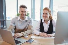 Portrait des cadres de sourire travaillant ensemble au bureau Images stock