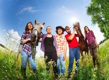 Portrait des cavaliers de horseback heureux avec deux chevaux Images stock