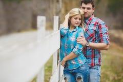 Portrait des chemises de port de jeunes couples heureux ayant l'amusement dehors près de la barrière dans le parc Photographie stock libre de droits