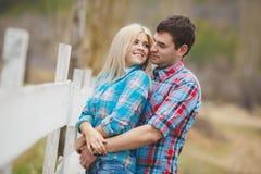 Portrait des chemises de port de jeunes couples heureux ayant l'amusement dehors près de la barrière dans le parc Photographie stock