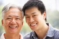 Portrait des chinesischen Vaters mit erwachsenem Sohn im Park lizenzfreie stockfotos