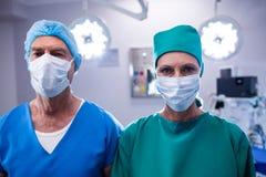 Portrait des chirurgiens portant le théâtre en fonction de masque chirurgical Photographie stock