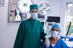 Portrait des chirurgiens portant le théâtre en fonction de masque chirurgical Image stock