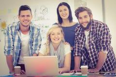 Portrait des collègues de sourire travaillant sur l'ordinateur portable image stock