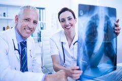 Portrait des collègues médicaux de sourire tenant le rayon X photographie stock