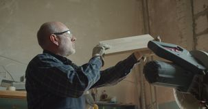 Portrait des contrôles supérieurs de charpentier la qualité ponçant le conseil en bois dans la fabrication clips vidéos