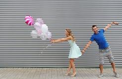 Portrait des couples élégants tenant des ballons de colorfull, sur le fond rayé de mur Photographie stock