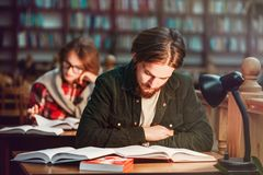 Portrait des couples des étudiants dans la bibliothèque Photos libres de droits