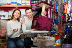 Portrait des couples achetant des établissements d'animal familier dans le petshop Photographie stock