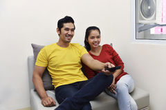 Portrait des couples asiatiques appréciant regardant la télévision ensemble Images libres de droits