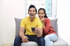 Portrait des couples asiatiques appréciant regardant la télévision ensemble Image stock