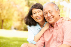 Portrait des couples asiatiques supérieurs se reposant en parc ensemble Photo stock