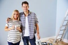 Portrait des couples décorant la crèche pour le nouveau bébé photo stock