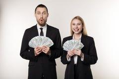 Portrait des couples dans les costumes noirs choqués tenant des billets de banque d'argent dans des mains photos libres de droits