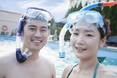 Portrait des couples de sourire dans la vitesse naviguante au schnorchel dans la piscine et de regarder l'appareil-photo Image stock
