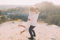 Portrait des couples de sourire de mariage de danse sur le fond supérieur de colline, de ville et de ciel Images stock