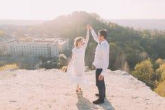 Portrait des couples de sourire de mariage de danse sur le fond supérieur de colline, de ville et de ciel Photographie stock libre de droits