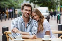 Portrait des couples de sourire se reposant au café de trottoir Photographie stock