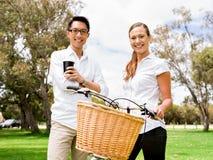 Portrait des couples de sourire se tenant en parc avec parler de vélo photographie stock libre de droits