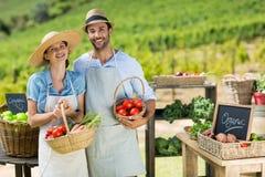 Portrait des couples de sourire tenant les légumes frais dans les paniers photo stock