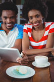 Portrait des couples de sourire utilisant le comprimé numérique en café Images stock