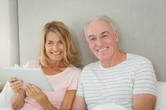 Portrait des couples de sourire utilisant le comprimé numérique sur le lit Images libres de droits