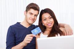 Portrait des couples faisant des emplettes en ligne à la maison Photographie stock libre de droits
