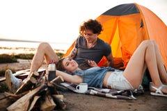 Portrait des couples gais détendant à la tente de camp Photos stock
