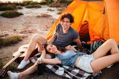 Portrait des couples gais détendant à la tente de camp Photographie stock libre de droits