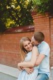 Portrait des couples heureux étreignant le fond riant de mur de briques Photo stock