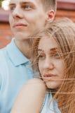 Portrait des couples heureux étreignant le fond riant de mur de briques Images stock