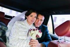 Portrait des couples heureux de nouveaux mariés dans la voiture après la cérémonie de mariage photos libres de droits