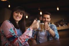 Portrait des couples heureux grillant des verres de bière au compteur Photo stock